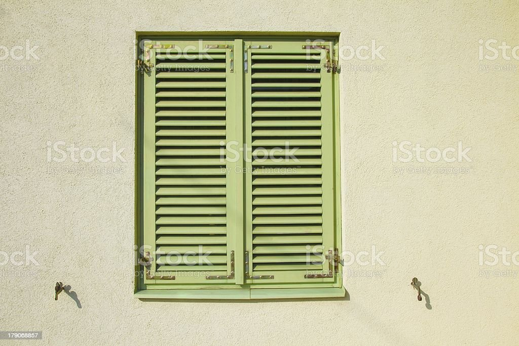 Closed green shutters on a bright yellow wall. royalty-free stock photo