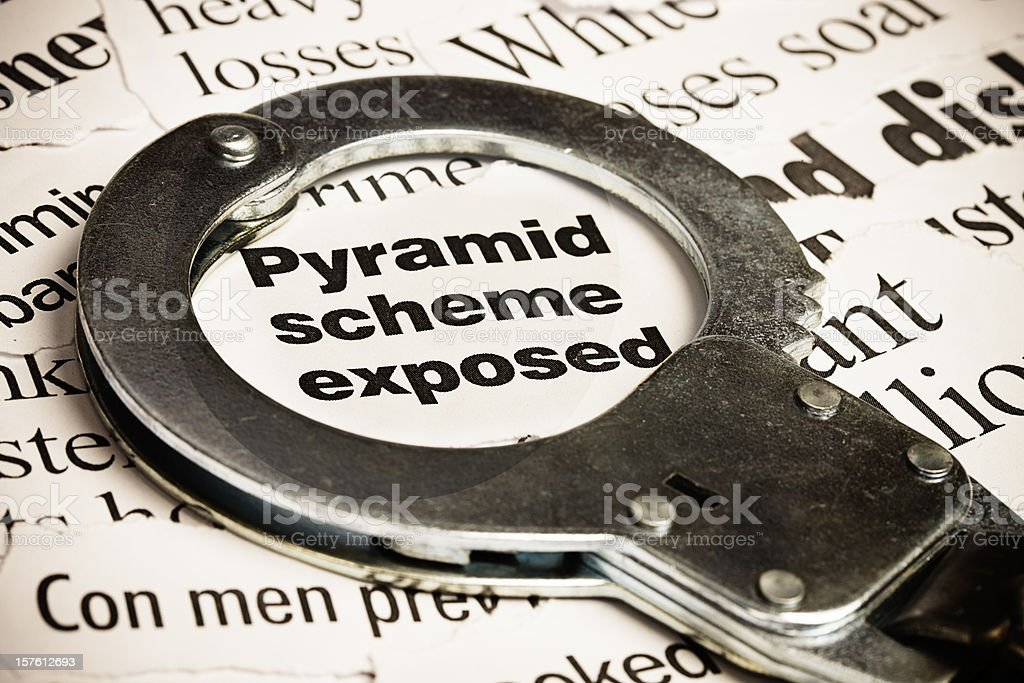 Closed handcuff on headline: pyramid scheme exposed stock photo