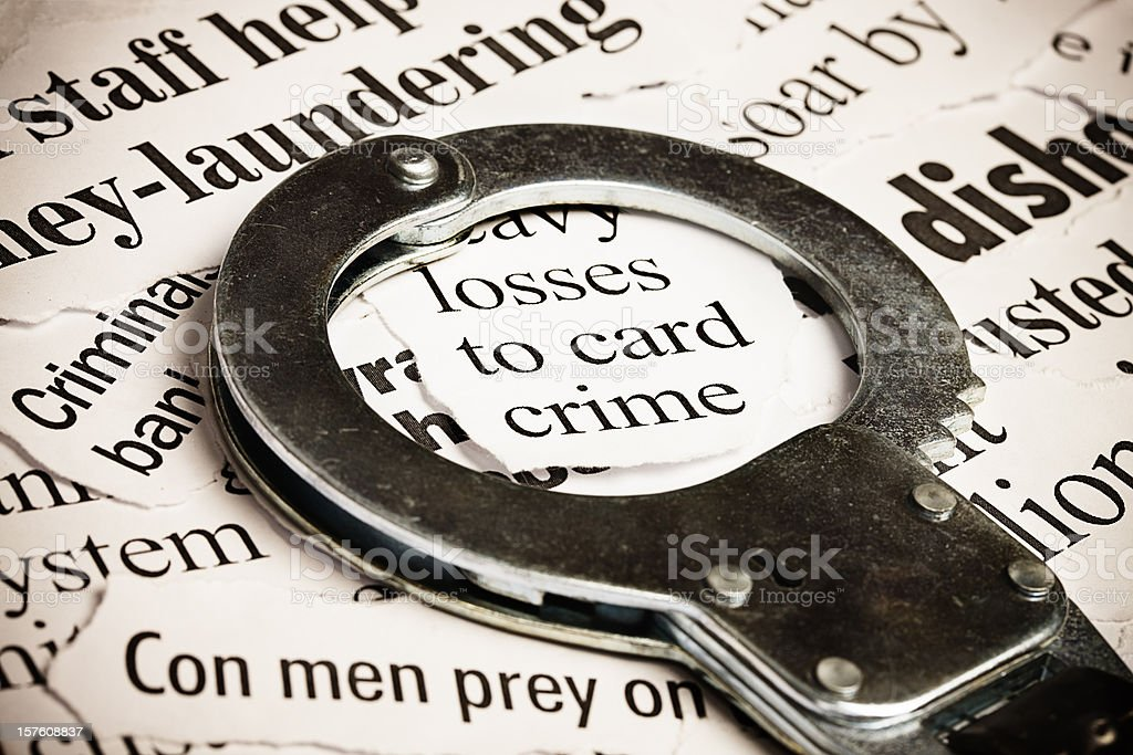 Closed handcuffs frame a headline on credit card crime stock photo