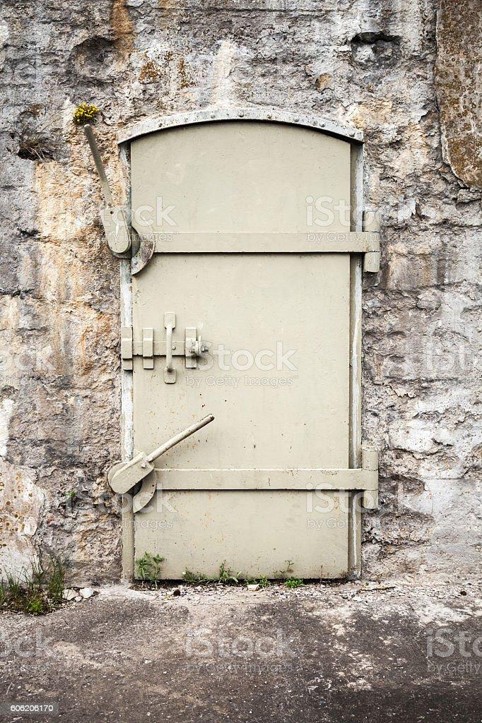 Closed massive metal door in old wall stock photo