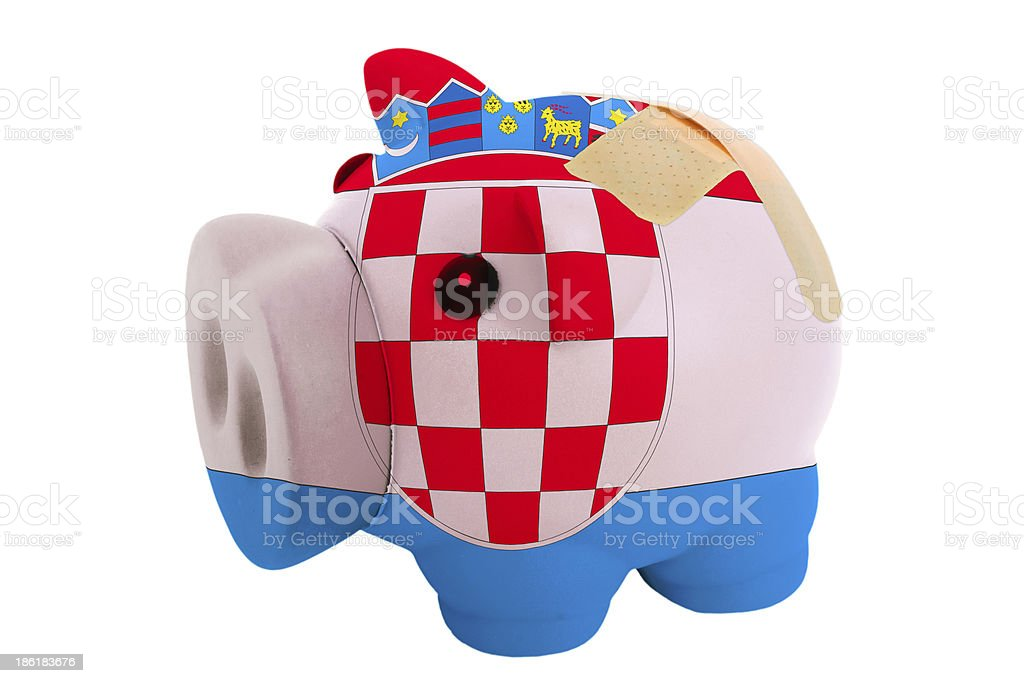 closed piggy rich bank with bandage in colors of croatia royalty-free stock photo