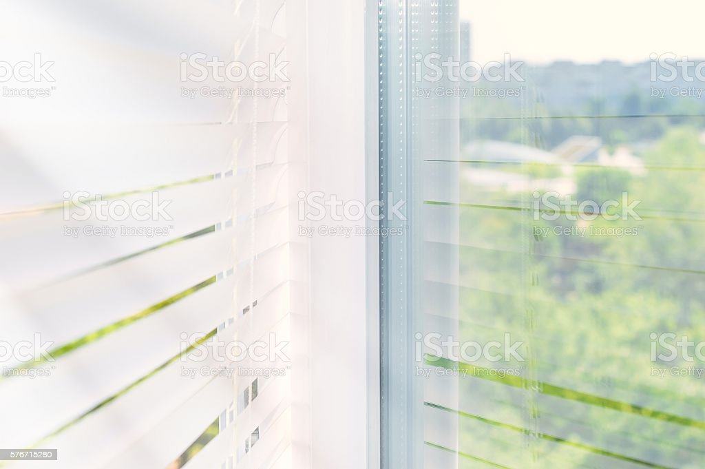 Closed plastic blinds on the window with the reflection in stock photo