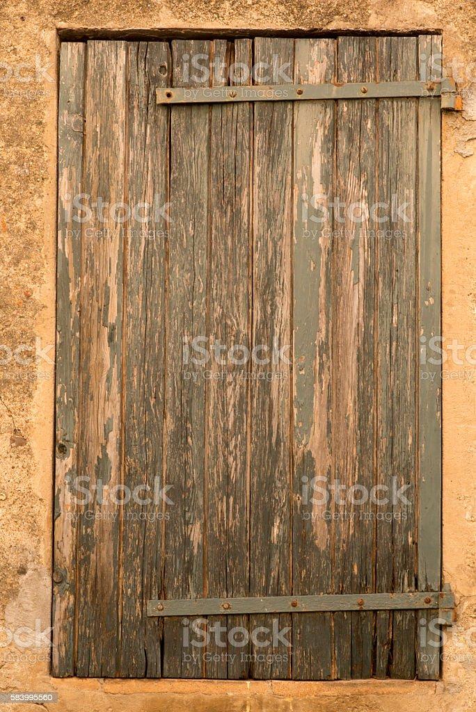 Closed shutter on a ochre wall stock photo