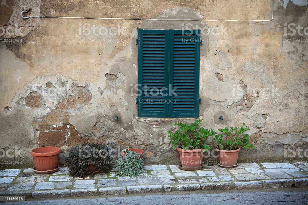 Closed shutters and potted plants in Tuscany royalty-free stock photo