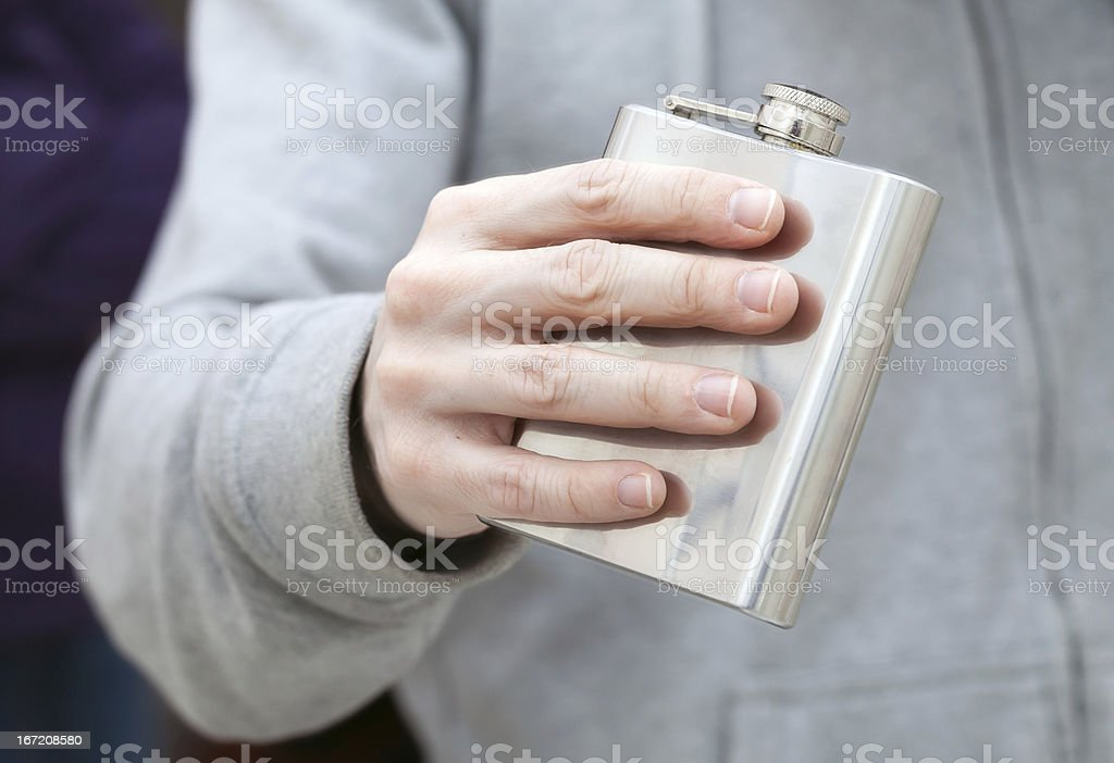 Closed steel small flask in man's hand stock photo