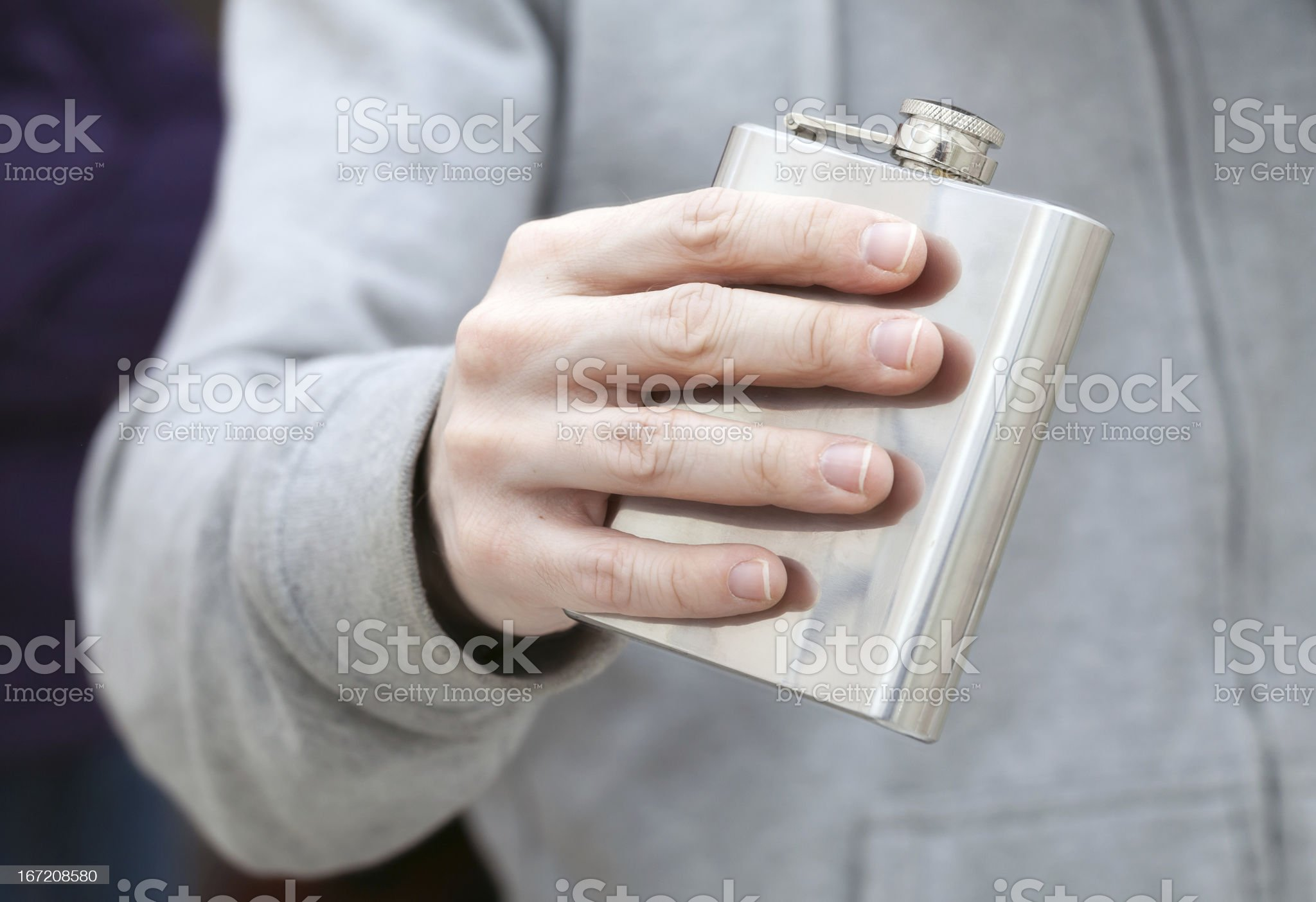 Closed steel small flask in man's hand royalty-free stock photo