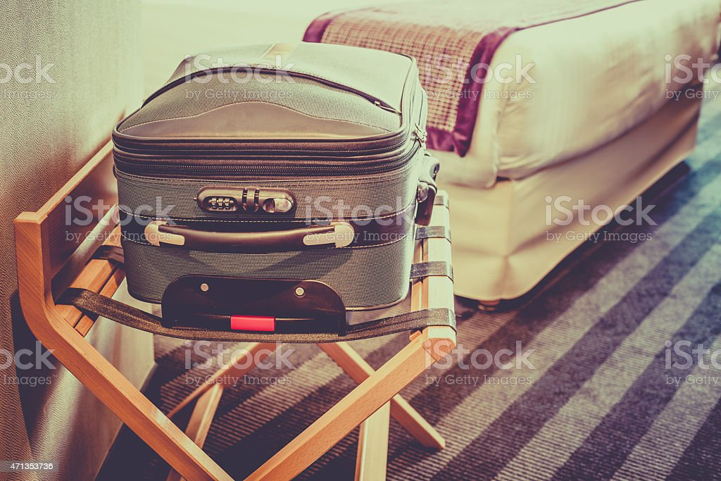 Closed suitcase sitting in clean hotel room stock photo