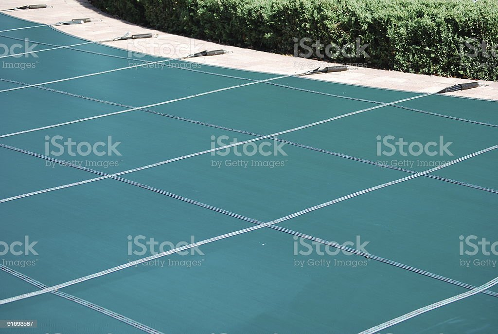 A closed swimming pool with a cover on top stock photo