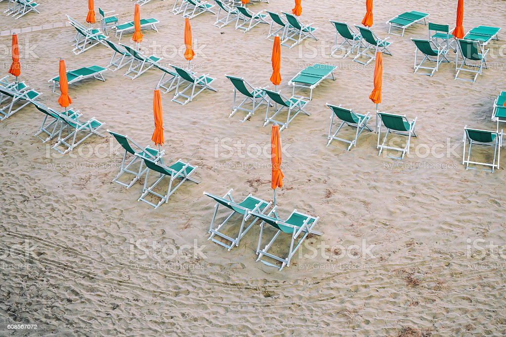 Closed umbrellas and sunbeds on a September beach stock photo
