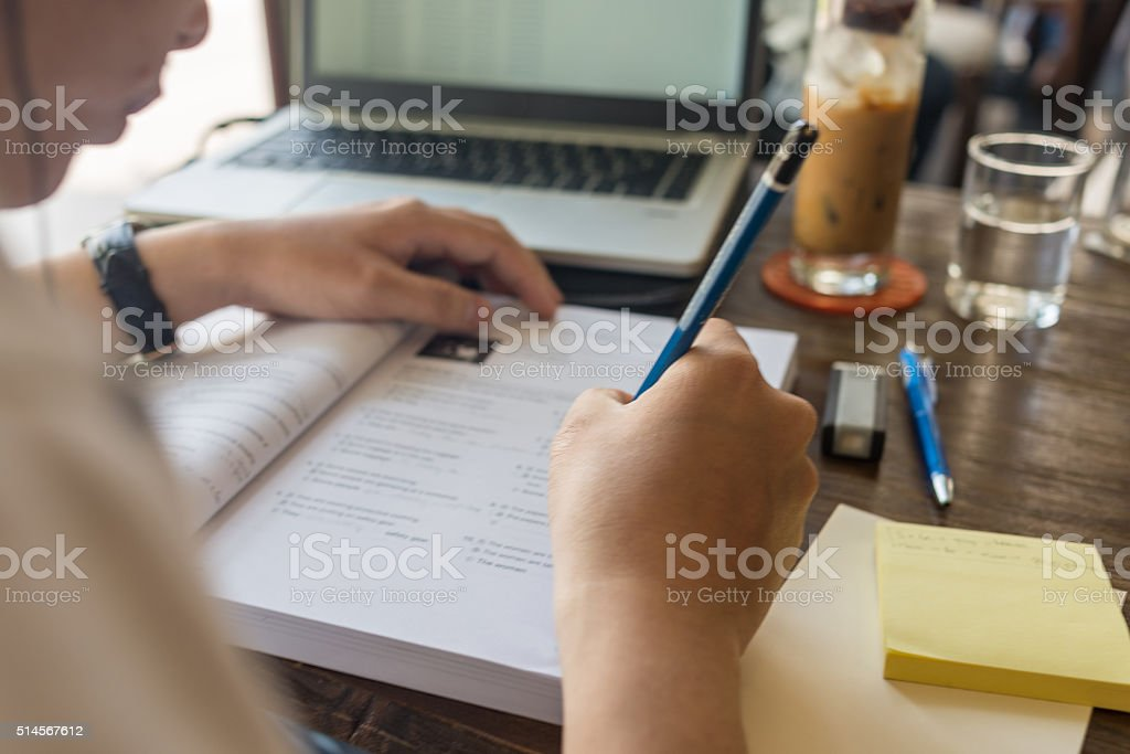 Closed up of young student answer questions on the book stock photo