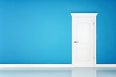 Closed white door on blue wall