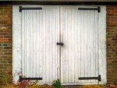 Closed white double barn doors set in a brick wall
