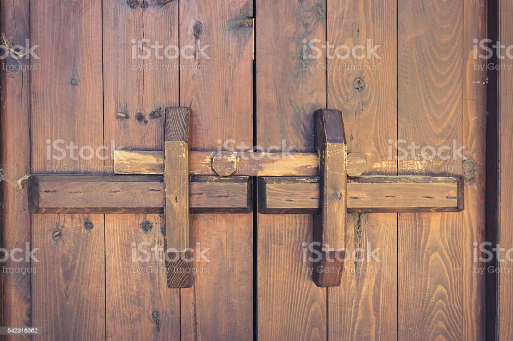 closed wooden door with locking bar , vintage stock photo