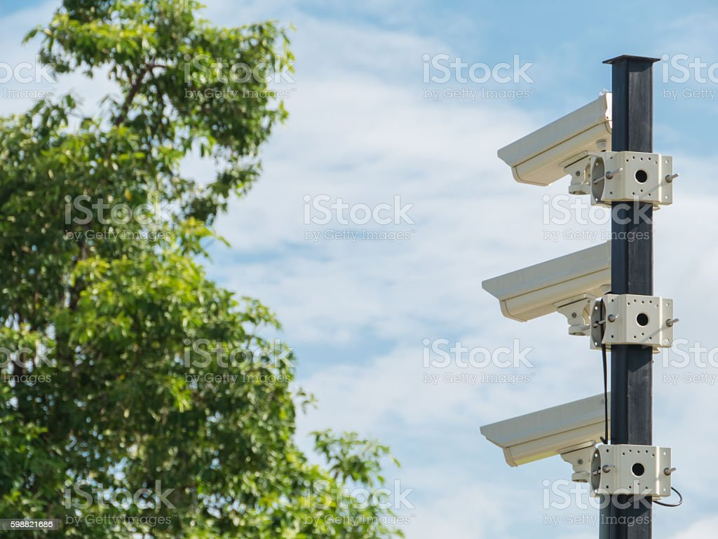 closed-circuit camera on white clouds background and blurred tre stock photo