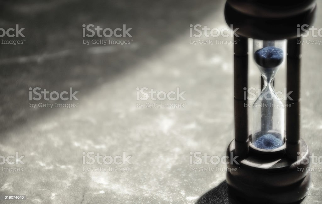 Closed-up hourglass with blue sand inside. Intentionally blur to stock photo