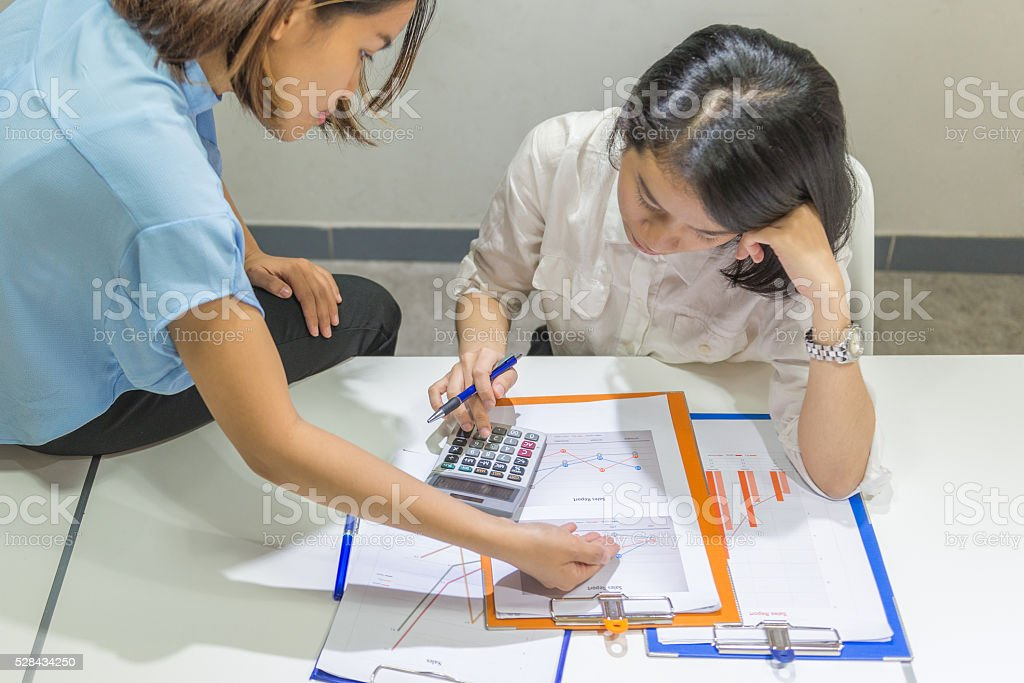 Closed-up of young Asian businesswoman calculate sales stock photo