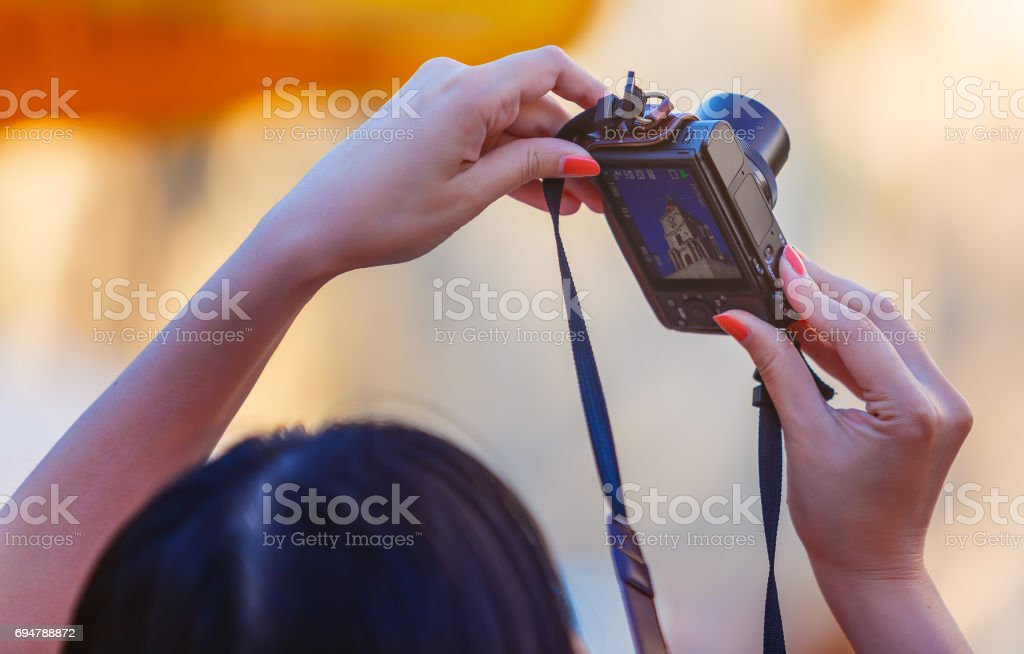Closely image of female hands holding photo camera mode on the screen. stock photo