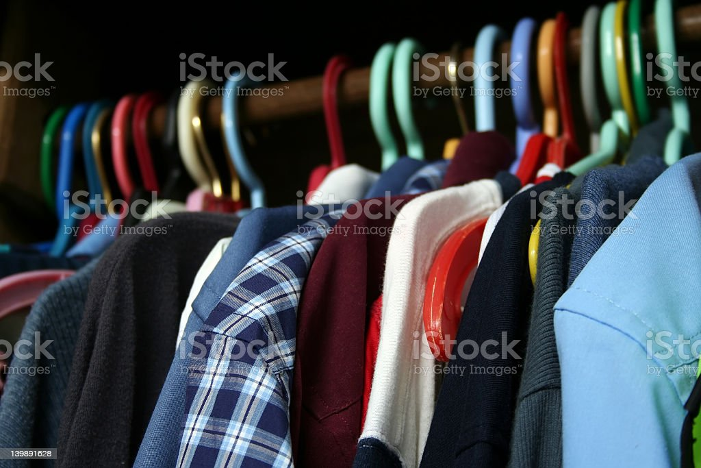 Closet rack with men's shirts hung up on colored hangers stock photo