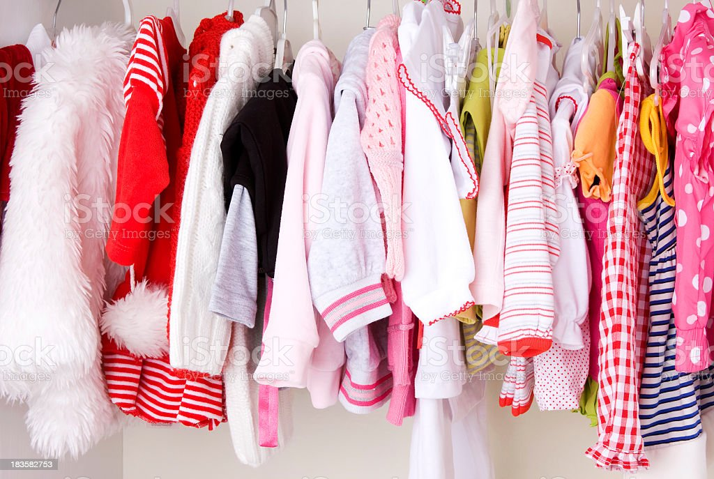 A closet that's full of baby's clothing  stock photo