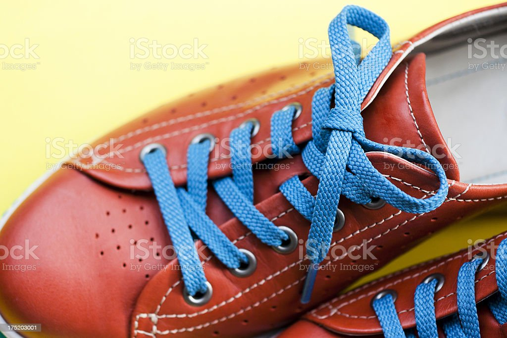 Closeu orange leather female shoe with blue sholaces, copy space stock photo