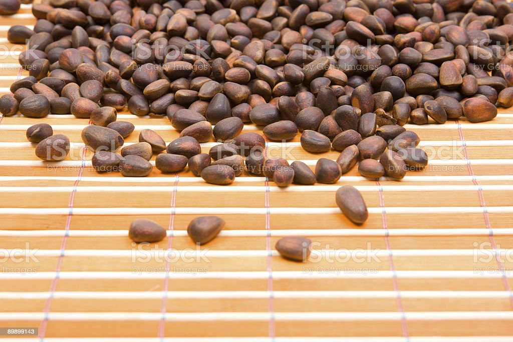 Close-up a pile of cedar nut on bamboo table-cloth royalty-free stock photo