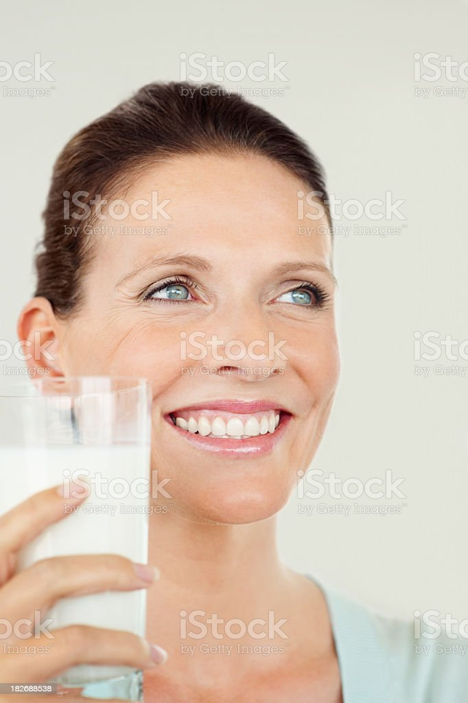 Closeup a thoughtful woman with glass of milk royalty-free stock photo