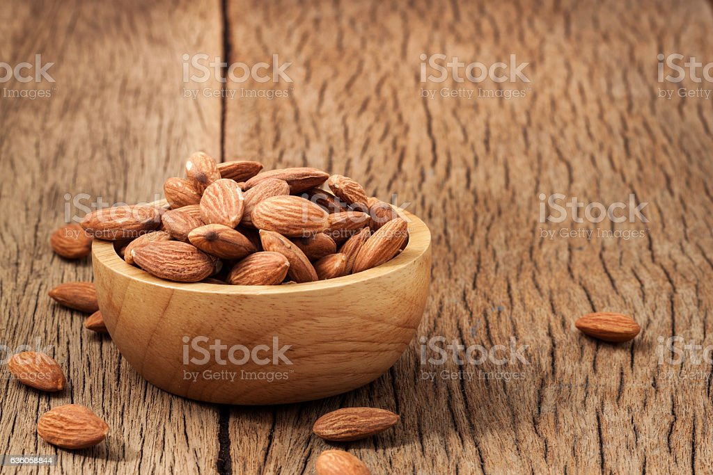 Closeup almonds kernels in wooden bowl with hemp sack on stock photo