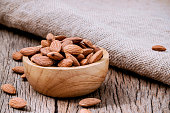 Closeup almonds kernels in wooden bowl with hemp sack on