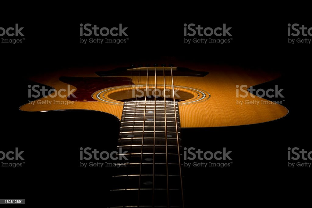 Close-up along the neck of an acoustic guitar in shadow royalty-free stock photo