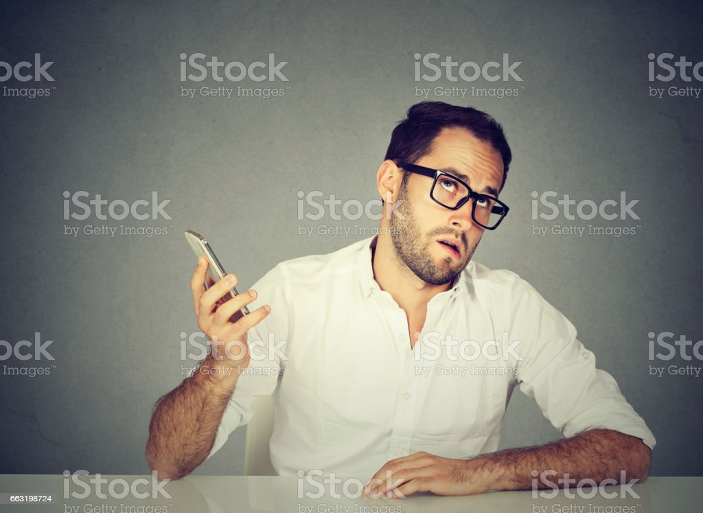 Closeup annoyed young man with cellphone stock photo
