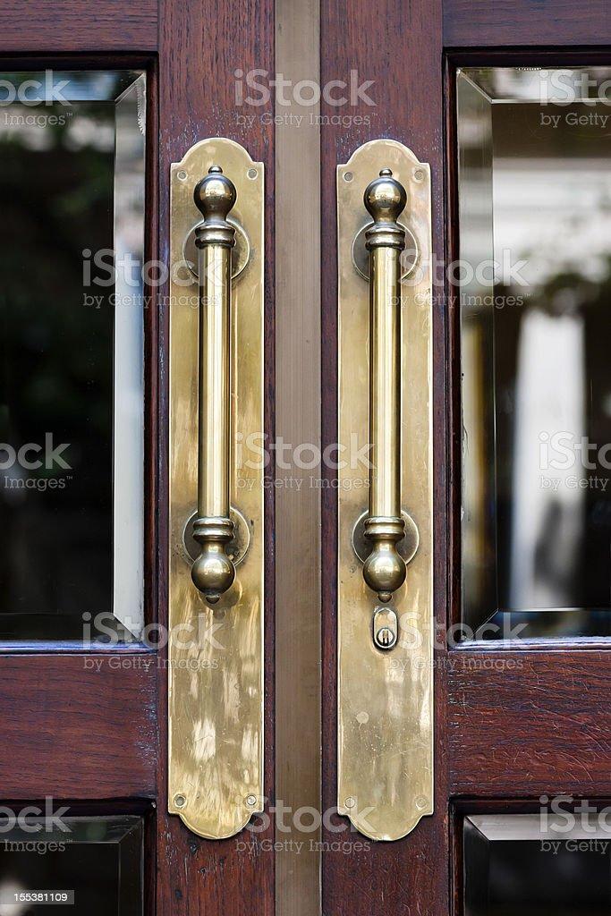 Closeup antique brass door handles on wooden door with glass stock photo
