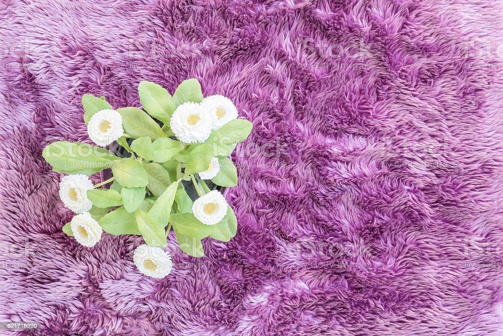 Closeup artificial flower on purple carpet textured background stock photo