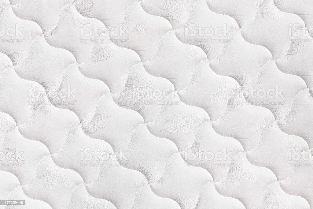 A close-up background of a white mattress stock photo
