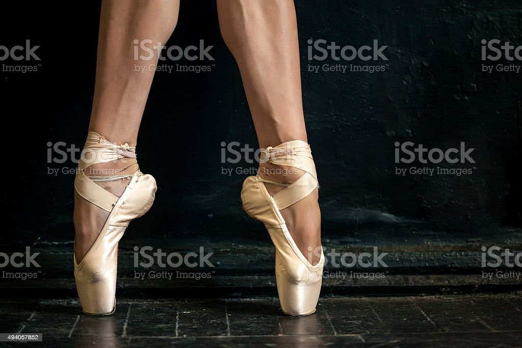 Close-up ballerina's legs in pointes on the black stock photo