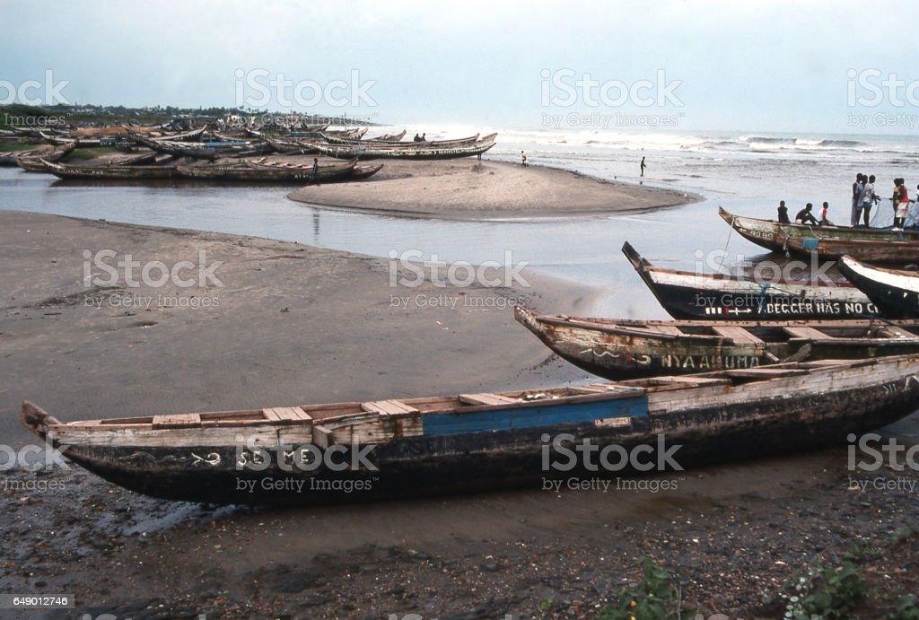 Closeup beached fishing boats along creek entering Atlantic Ocean near Accra Ghana Africa stock photo