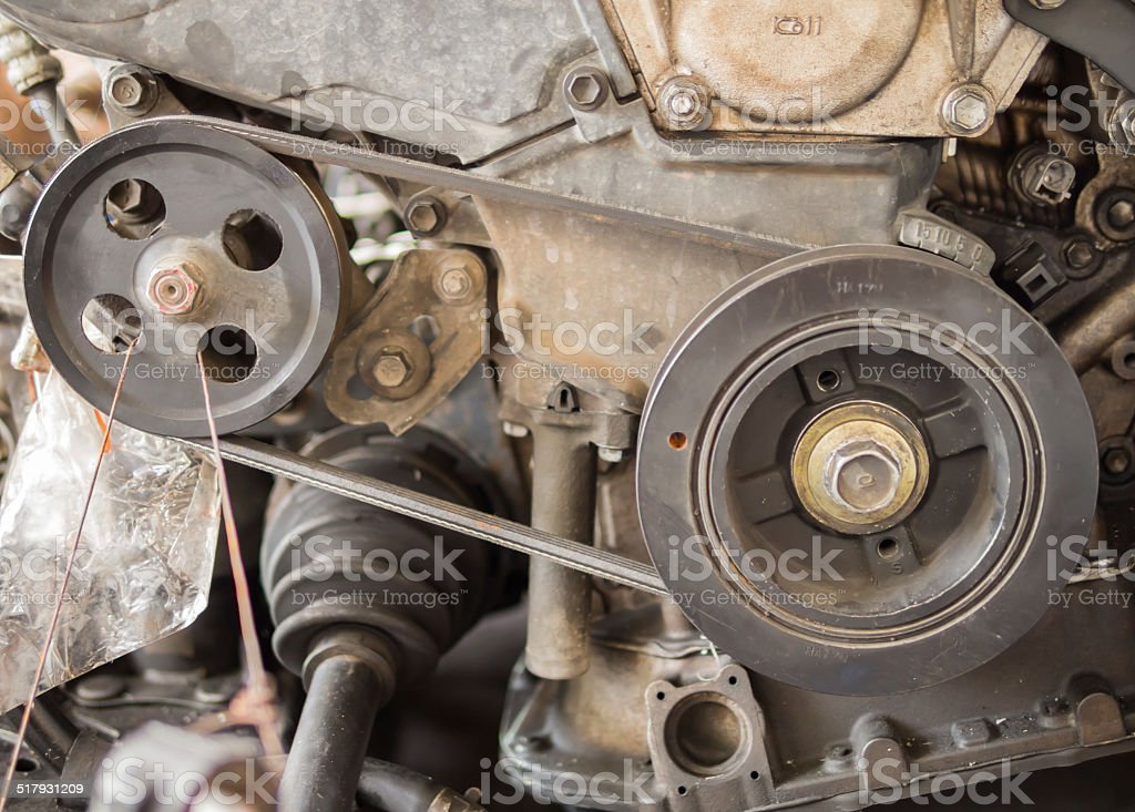Closeup belt and rusty pulley of car engine in garage stock photo