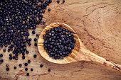 Closeup black pepper in wooden spoon on teak wood table.