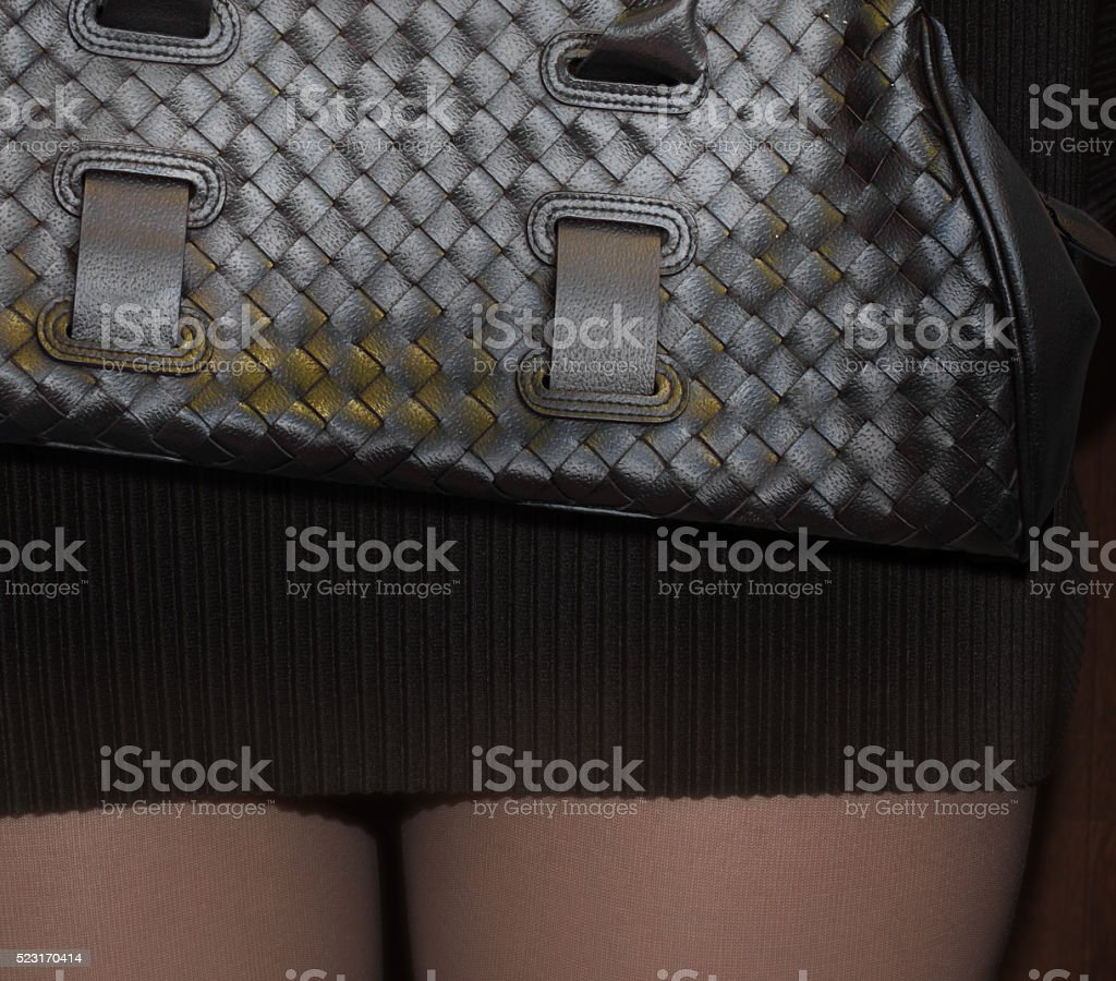 closeup braided leather purse and pleated black skirt stock photo