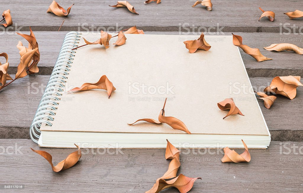 Closeup brown note book on wooden table with dried leaves stock photo