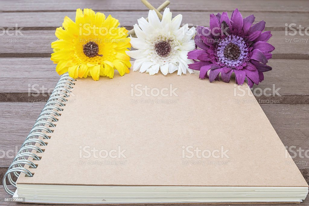Closeup brown note book with colorful faked flower stock photo