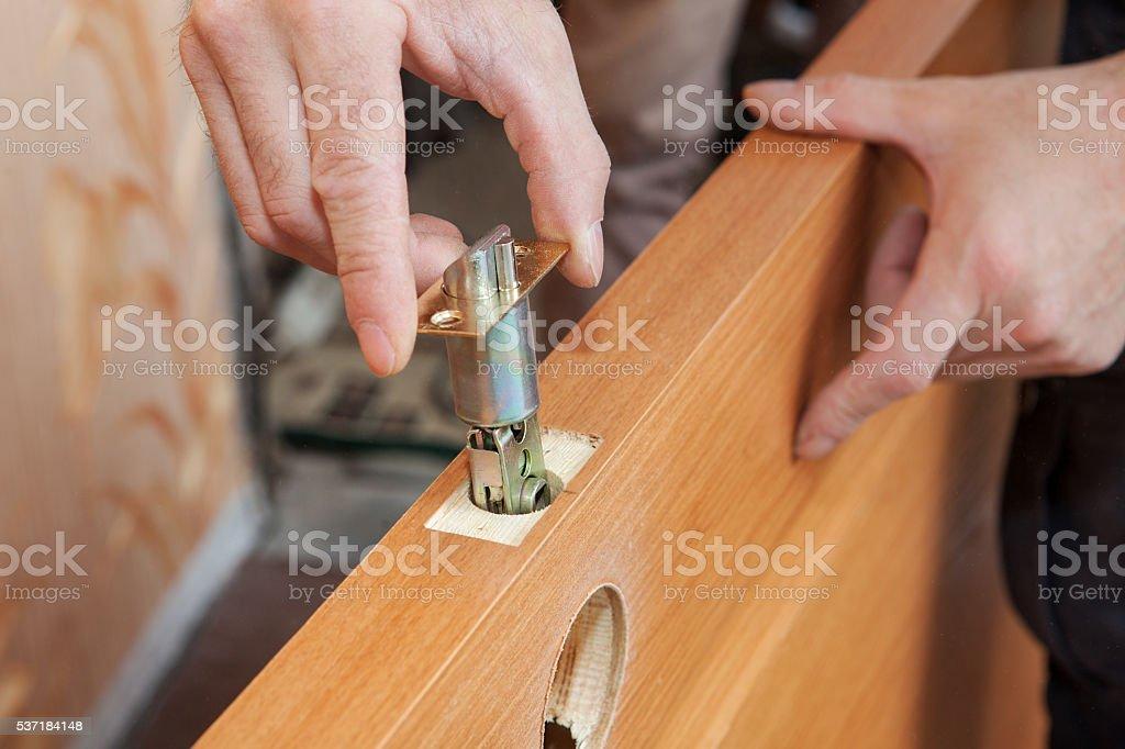Close-up carpenter hands door lock installation. stock photo