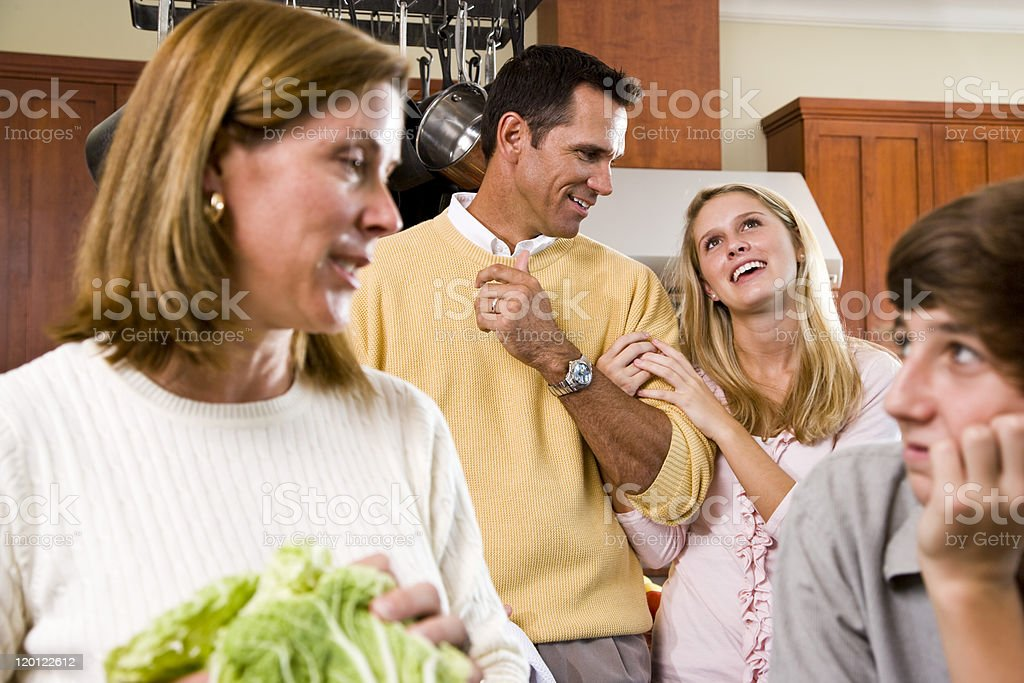 Closeup cheerful family of four in kitchen conversing royalty-free stock photo