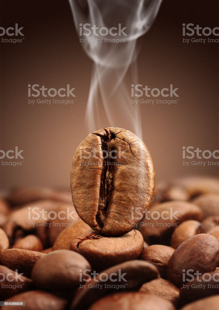 Closeup coffee bean with smoke on brown background stock photo