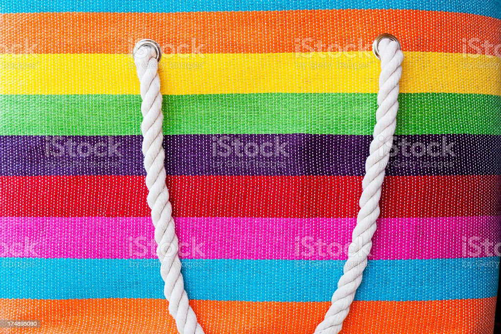 Closeup colourful stripes beach bag with white rope royalty-free stock photo