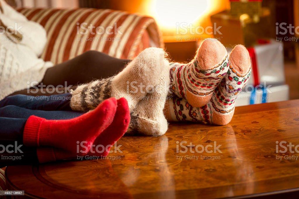 Closeup conceptual shot of family warming feet at fireplace stock photo