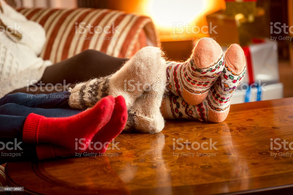 Closeup conceptual shot of family warming feet at fireplace stock photo