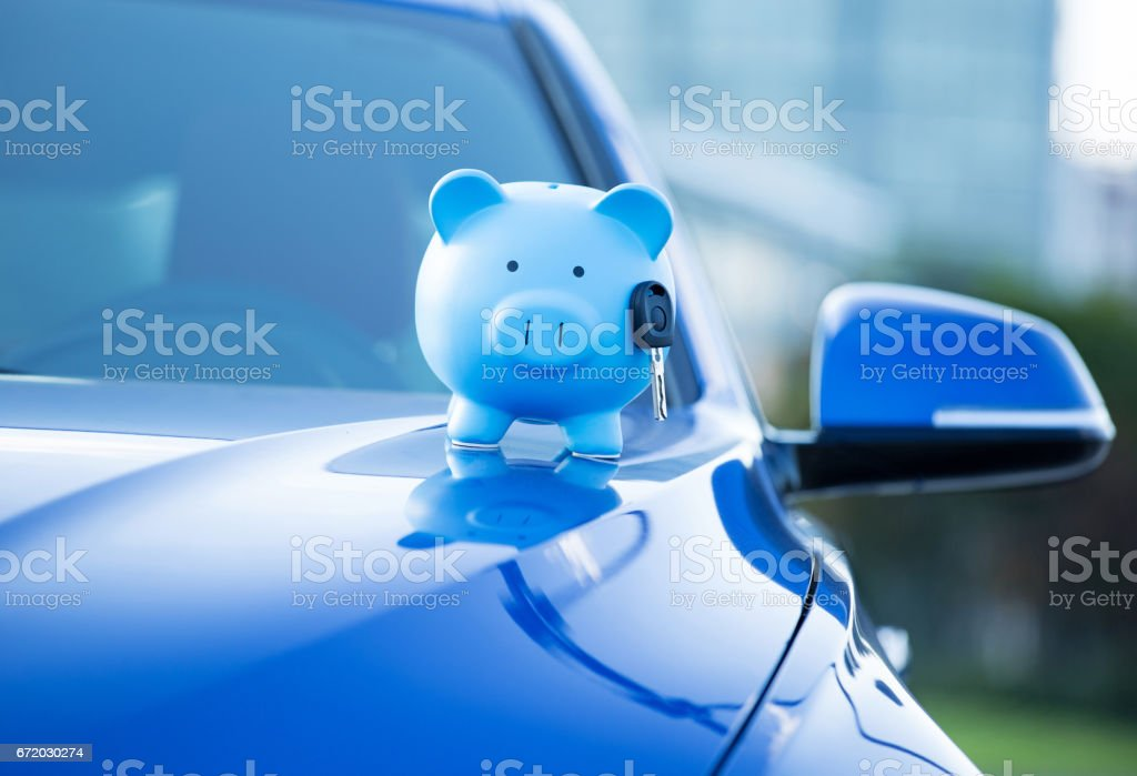 Closeup cropped image blue new car with piggy bank and key on hood, isolated outside corporate building stock photo