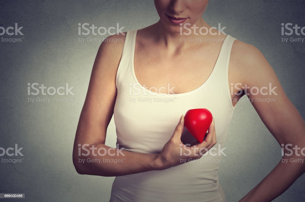 Closeup cropped image young woman holding red drop of blood isolated on gray wall background stock photo