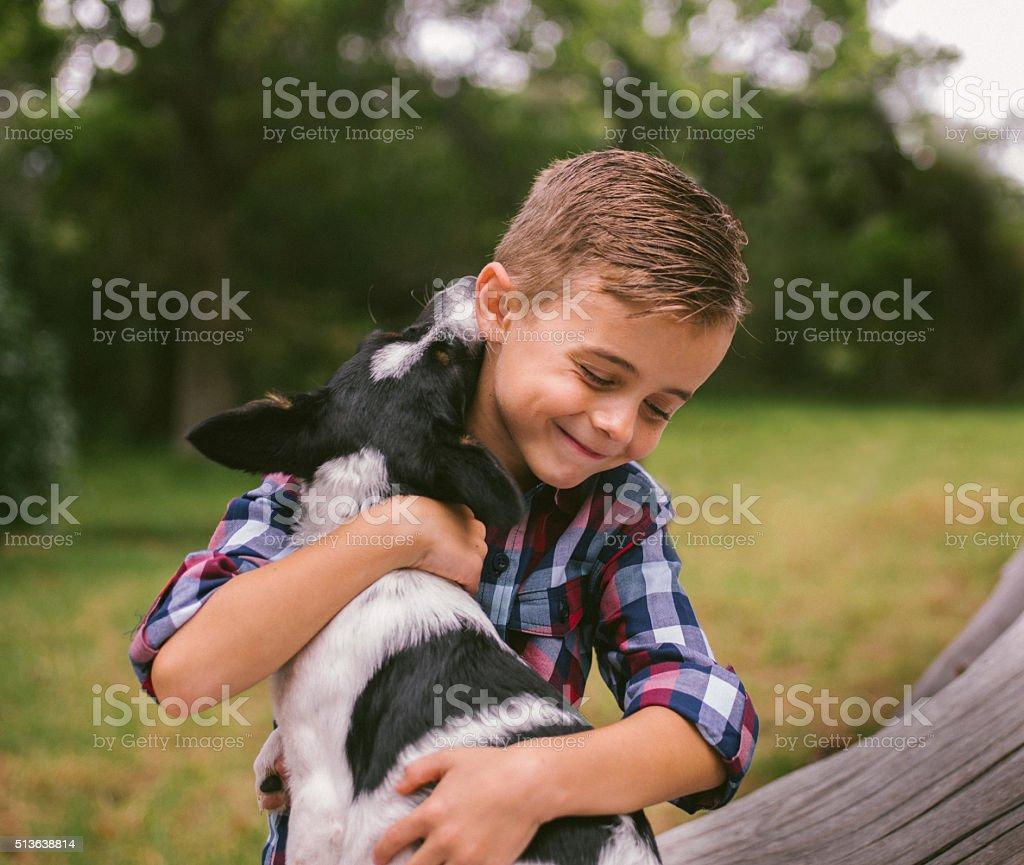 Closeup cute rascal boy gives his puppy a big hug stock photo