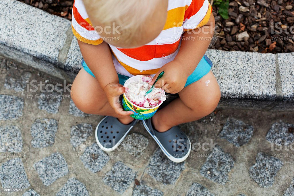Close-up detail of child eating ice cream. stock photo